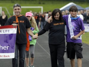 From left, Jon and Seleste Lucas walk with their son and cancer survivor, Nicolas Lucas during the first Relay for Life at Woodland Regional High School in Beacon Falls on Saturday. The event was established by Lucas, who is a senior at Woodland. -REPUBLICAN-AMERICAN