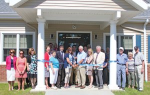 Region 16 Board of Education Chair Sheryl Feducia and Vice Chair Robert Hiscox, center, cut a ribbon surrounded by local officials during a ceremony June 18 at the district's new office in Prospect to officially open the office. –ELIO GUGLIOTTI
