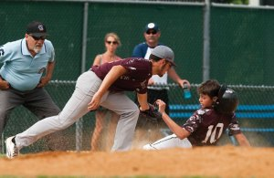Naugatuck's Derek Sampaio (24) tags out Overlook's Drew Colavecchia (10) at third July 15 during a Sandy Koufax North American Regional at Municipal Stadium in Waterbury. Naugatuck lost the game, 15-0. –REPUBLICAN-AMERICAN