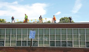 Workers make repairs to the roof of the former Community School in Prospect on Tuesday. The town plans to use the building as a community center. –LUKE MARSHALL