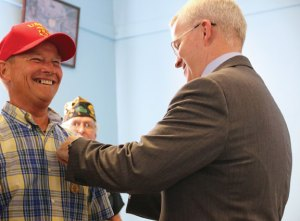 Connecticut Department of Veterans' Affairs Commissioner Sean Connolly, right, pins a Connecticut Veterans Wartime Service Medal on veteran Patrick O'Neill July 28 during a ceremony at the American Legion Post 17 hall in Naugatuck. –LUKE MARSHALL