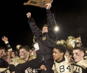 Then-Woodland football coach Chris Anderson holds up the state championship trophy while getting carried on the shoulders of his players in December 2004 after the Hawks beat Holy Cross, 35-0, in the Class SS state championship game. The state title was the first in Woodland's history. –RA ARCHIVE