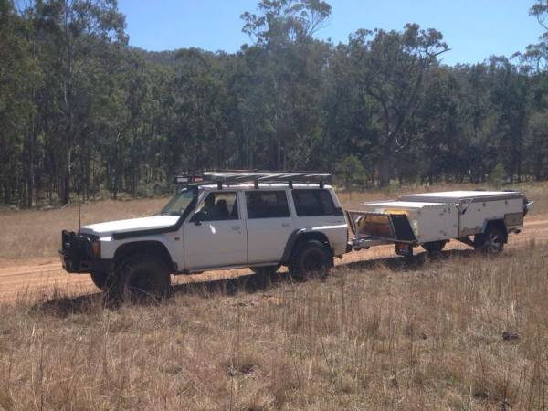 Photo of white hard floor forward fold camper trailer behind 4wd