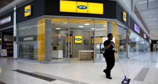 A worker sweeps past an outlet of South Africa's MTN Group in Johannesburg