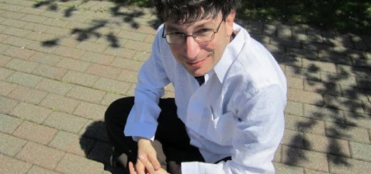 James Altucher sitting on a brick patio with a white t shirt on and grey dress slacks