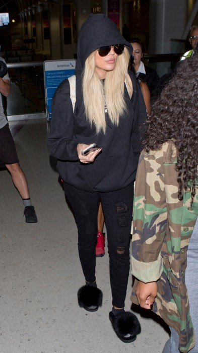 Khloe Kardashian wearing a Black Hoodie, Sunglasses and fluffy slippers was seen arriving into LAX on a flight from New York City