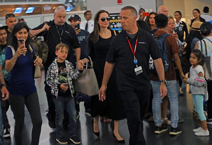 Angelina Jolie arriving to JFK Airport with her two Sons Knox and Maddox she holds Knox hand while Maddox trails behind them in New York City.