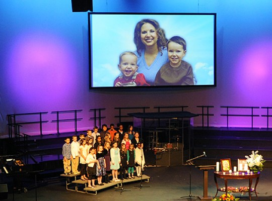 A photo of Susan Cox Powell and her sons Charlie, right, and Braden, left, is shown as a children's choir performs during a funeral service for Charlie and Braden Powell at Life Center Church in Tacoma, Washington, on Saturday, February 11, 2012. Braden, 5, and Charlie, 7, were killed by their father, Josh Powell, February 5, 2012. (Lui Kit Wong/Tacoma News Tribune/MCT via Getty Images)