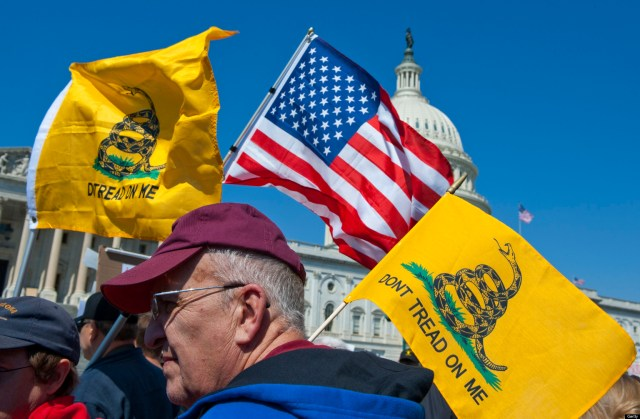 UNITED STATES Ð APRIL 6: Tea party activist on the East Front of the U.S. Capitol hold up signs and flags during a rally on Wednesday, April 6, 2012, days before a possible federal government shutdown. (Photo By Douglas Graham/Roll Call)