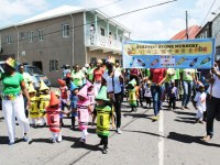 Mrs Patricia Dasent (extreme left) leads children and staff members of Steppin' Stone Nursery during the Child Month Parade that was held in Charlestown on Friday June 6.