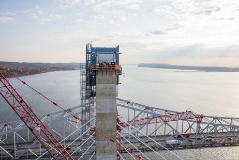 November 16, 2016 - Crew members stands atop a main span tower.