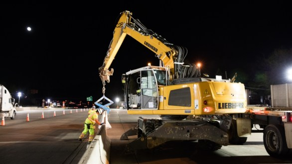 April 23, 2016 - Workers help align a road barrier near the Tarrytown toll plaza in preparation for a new lane configuration.