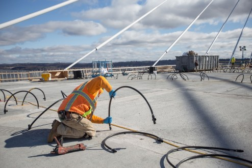 March 29, 2017 - A worker prepares the pumping system that will apply grout underneath the bridge's concrete deck panels.