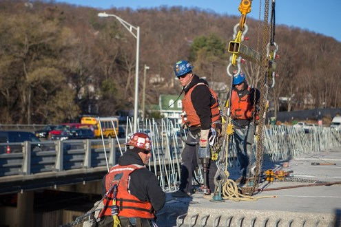 December 16, 2015 - Crew members install a new road deck panel.