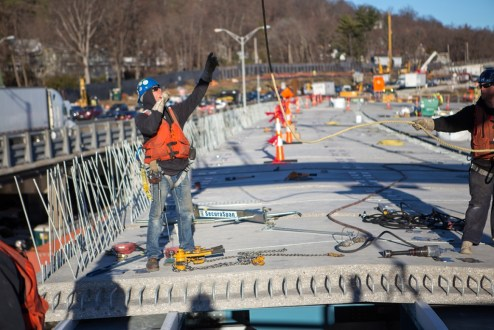 December 16, 2015 - Crew members help guide the installation of a new road deck panel.