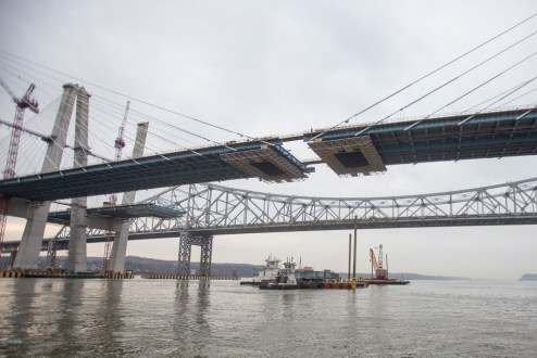 March 25, 2017 - Tugboats guide a barge carrying the final section of structural steel for the westbound bridge.