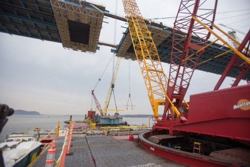 March 25, 2017 - Workers rig the final section of westbound steel to a pair of barge-based cranes.