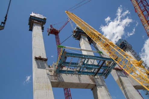 June 7, 2016 - The first section of structural steel on the main span is raised more than one hundred feet above the river.