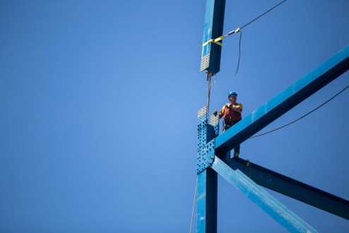 June 22, 2016 - An ironworker helps guide the installation of a steel beam on a temporary support tower.