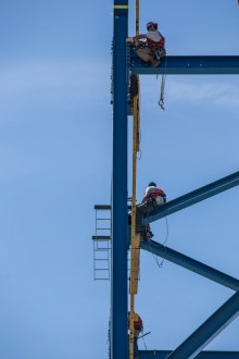 June 22, 2016 - Ironworkers assemble an enormous support tower for a new crane that will assemble the bridge's roadway.