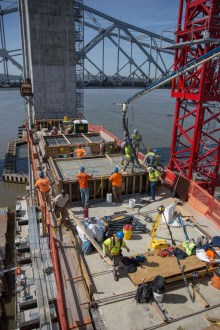 May 14, 2016 - Crew members pour concrete that will support the main span's structural steel.
