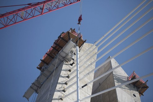 February 23, 2017 - One of the project's red tower cranes raises a stay cable to an anchor point.