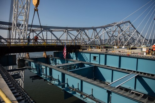 September 25, 2017 - Barge-based cranes raise the final section of main span steel.