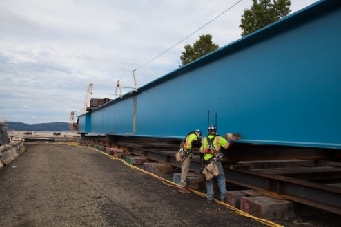 October 1, 2015 - Workers prepare a massive steel-blue girder assembly for installation from the Westchester abutment.
