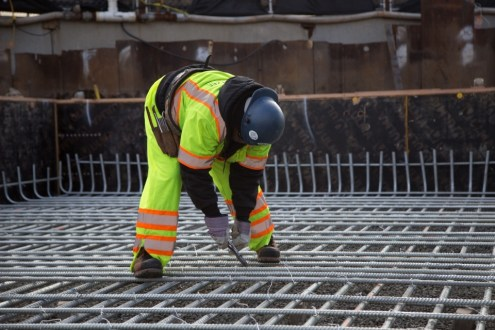 January 20, 2015 - An iron worker ties rebar with steel wire.