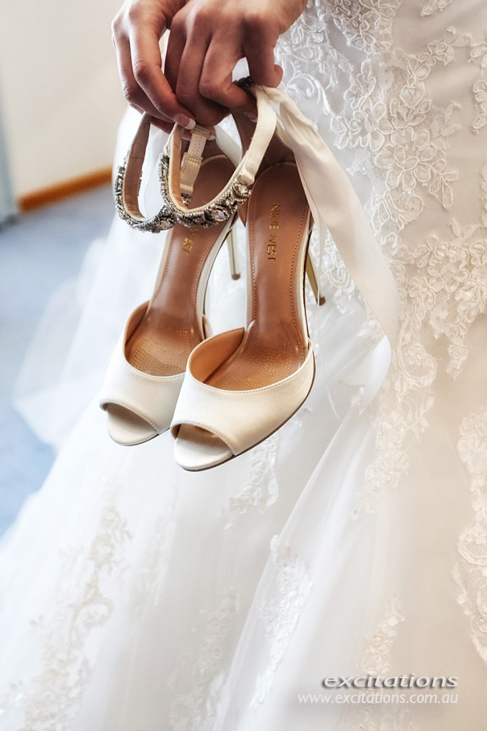 Close up of brides shoes being held in front of her bridal gown. Wedding photos in Mildura by Excitations.