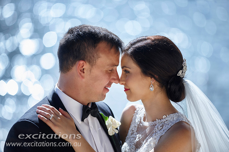 Close up of bride and groom with sparkling water as the backround. Wedding photos by Mildura photographers Excitations.
