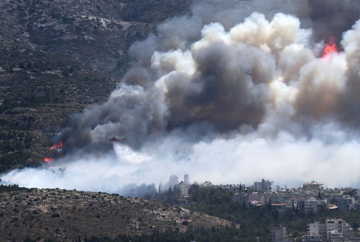 A firefighting helicopter drops water at a raging wildfire at the Kareas suburb, east of Athens, Greece July 17, 2015. Dozens of Athens residents fled their homes on Friday as wildfires fanned by strong winds and high temperatures burned through woodland around the Greek capital, sending clouds of smoke billowing over the city.    REUTERS/Alkis Konstantinidis