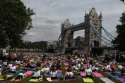 Yoga enthusiasts in London with Tower Bridge in the background