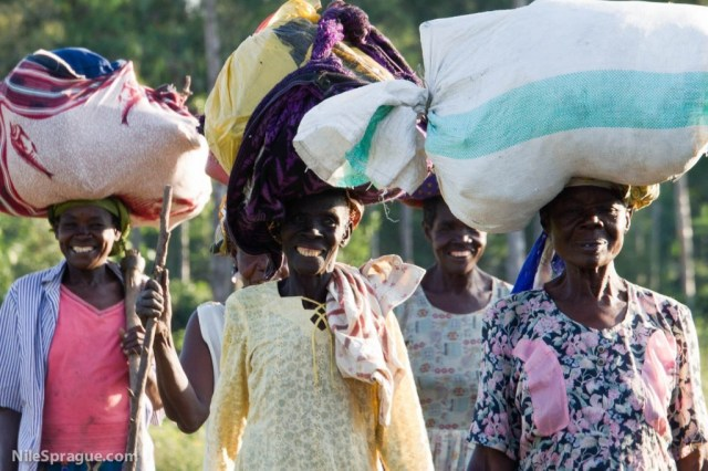 Women carrying sacks home on their heads at the end of the day after market, Odeso Village, Kisumu, Kenya