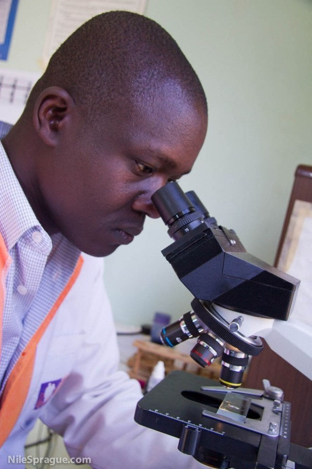 Photo: Technician examining lab samples with microscope at KMET clinic, Kisumu Medical and Education Trust, Kisumu, Kenya.