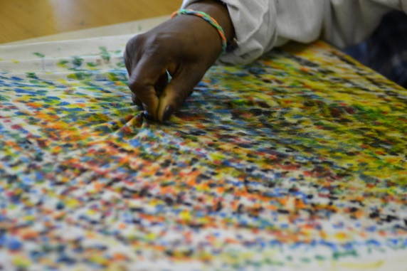 Workshop participant painting their T-shirt with textile crayons