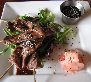 Skewers of orange glazed beef with sesame seeds and a tangy teriyaki sauce