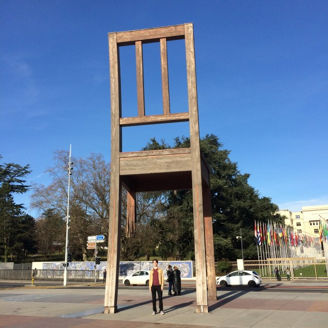 Nicholas Haubrich in front of a 3-legged chair in front of the UN.