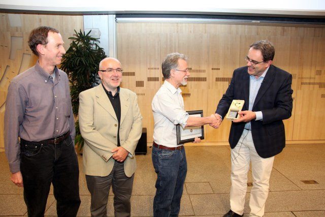 George Alverson receiving his award from, left to right, Bill Gary (UC Riverside), current publications committee co-chair, Roberto Tenchini (Universita di Pisa and INFN), and Tiziano Camporesi (CERN), CMS spokesperson).