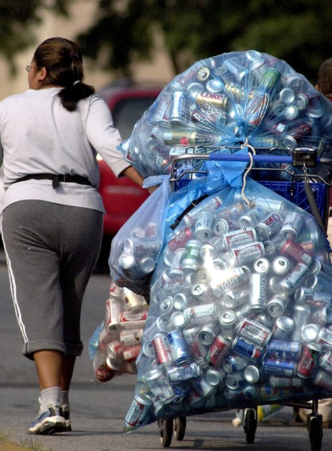 A woman with bags of recycleable containers.