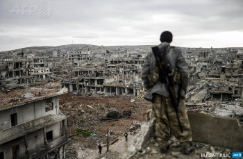 Musa, a 25-year-old Kurdish marksman, stands atop a building as he looks at the destroyed Syrian town of Kobane, also known as Ain al-Arab, on January 30, 2015 (Photo: Bulent Kilic).
