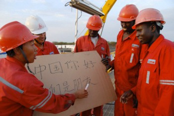 Chinese employee of Zhongyuan Petroleum Exploration Bureau (ZPEB) of Sinopec teaches Sudanese workers reading the Chinese characters shown on a board, which means Hello China, We Are Friends, at a jobsite for oil drilling in Sudan, Africa, 15 June 2008.
