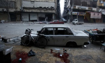Blood stains are seen on the pavement after artillery mortar shells landed on the opposite side of a bread shop operated by the civilian arm of the Free Syrian Army in the Bustan Al-Qasr neighborhood of Aleppo, on December 3, 2012. (Photo: Javier Manzano / AFP / Getty Images).