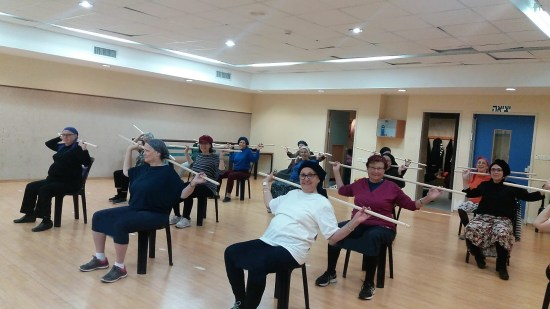 New Olim senior women doing a stretch exercise class with broomsticks