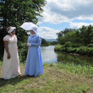 two ladies in Regency costume beside the river