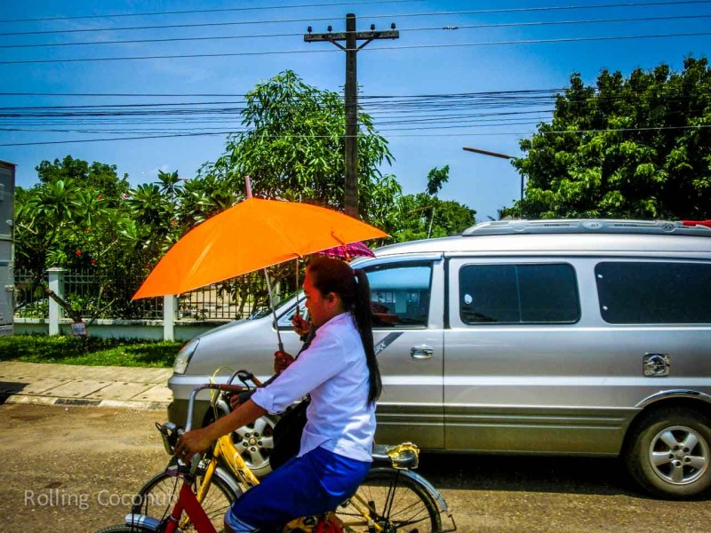 Laotian girl using Sun Umbrella on Bicycle in Vang Vieng Laos Rolling Coconut Ooaworld Photo Ooaworld