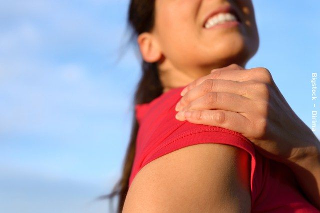 Fitness woman suffering from shoulder injury while exercising. Sky copy space background.