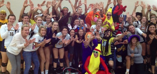 The Gold Crew, along with several volleyball players, celebrates after a win. The crew has several chants they recite during various sporting events, along with traditions performed following wins (see sidebar).