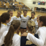 The varsity team huddles in the middle of the third set.