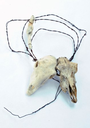 "April Marie Hale, ""Like Sheep, Waiting,"" sheep skull, toy gun, felted wool, barbed wire."